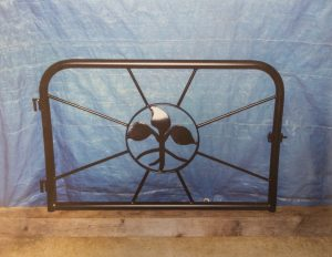 sleek metal fireplace cover with a sprout symbol